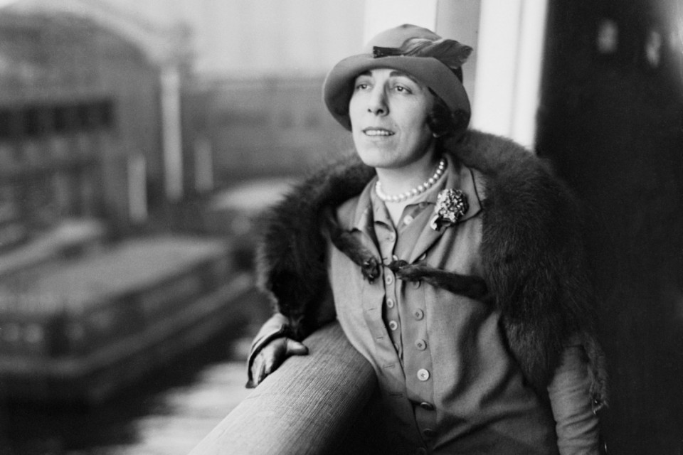 Photograph of Edna Ferber, wearing a hat, pearls, fur stole, suit, and gloves, leaning on a railing overlooking a body of water.