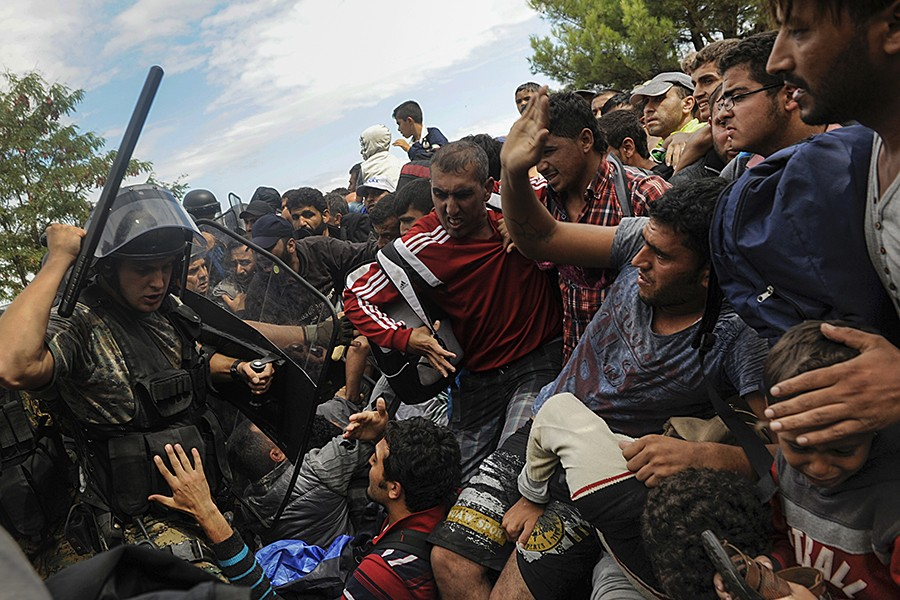 A Macedonian police officer raises his baton towards migrants to stop them from entering into Macedonia at Greece's border near the village of Idomeni, Greece (Alexandros Avramidis, Thomson Reuters - August 22, 2015).