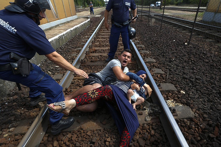 Hungarian policemen stand over a family of immigrants who threw themselves onto the track before they were detained at a railway station in the town of Bicske, Hungary (Laszlo Balogh, Thomson Reuters - September 3, 2015).